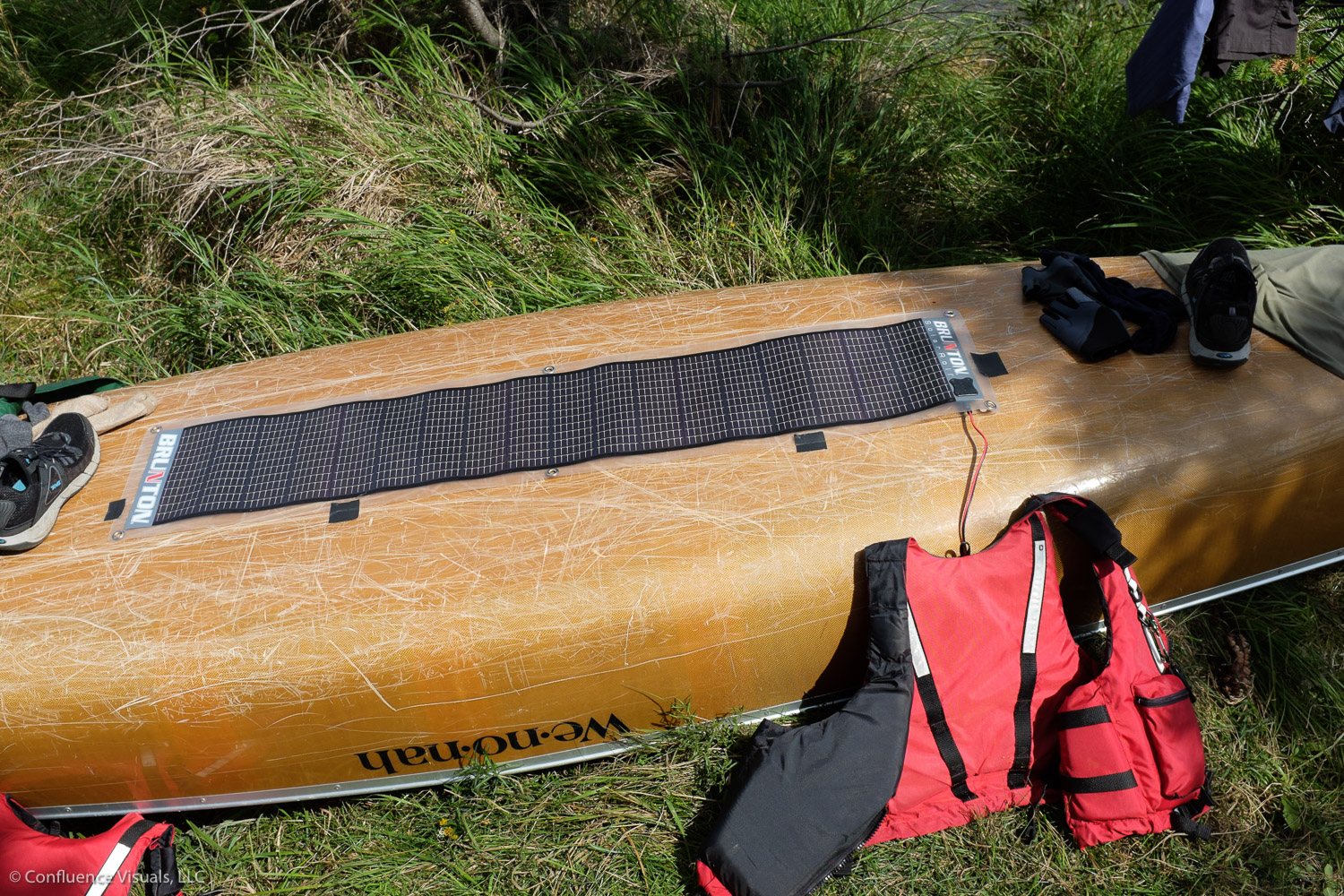 Charging the batteries (hiding from the sun under the PFD) Note the gaffing tape holding solar array to the boat.